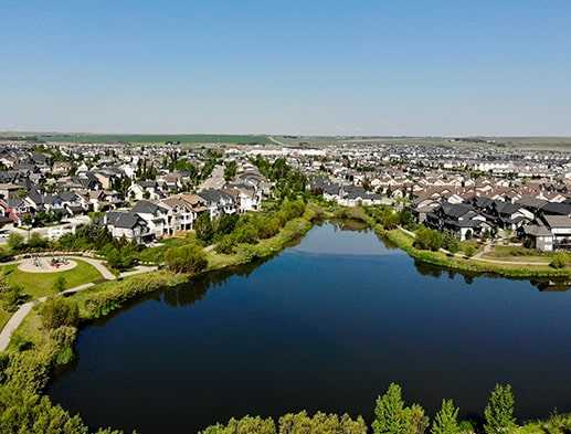 A picture of the massive pond and walkways in Cooper's Crossing Airdrie Alberta